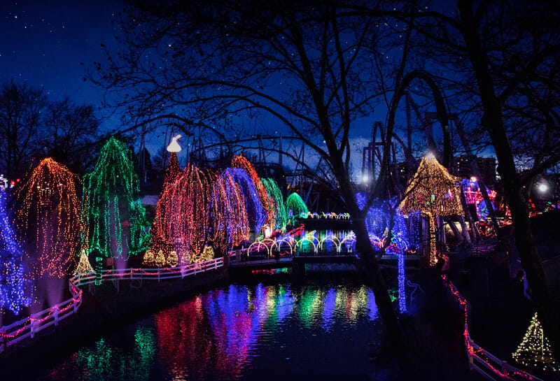 Christmas lights reflecting off the stream with rides lining both sides
