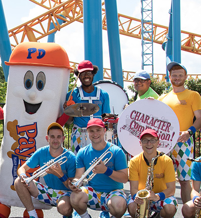 Band posing with their instuments and Payday Hershey's Character in front of Fahrenheit Rollercoaster