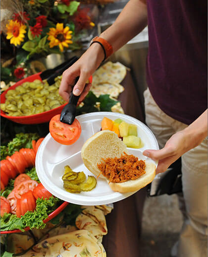 Sandwich, pickles, fruit being put on a styrofoam plate