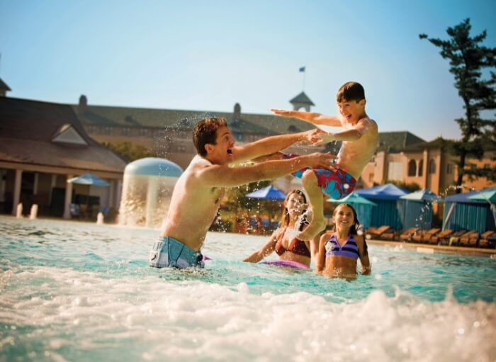 Family playing in outdoor pool