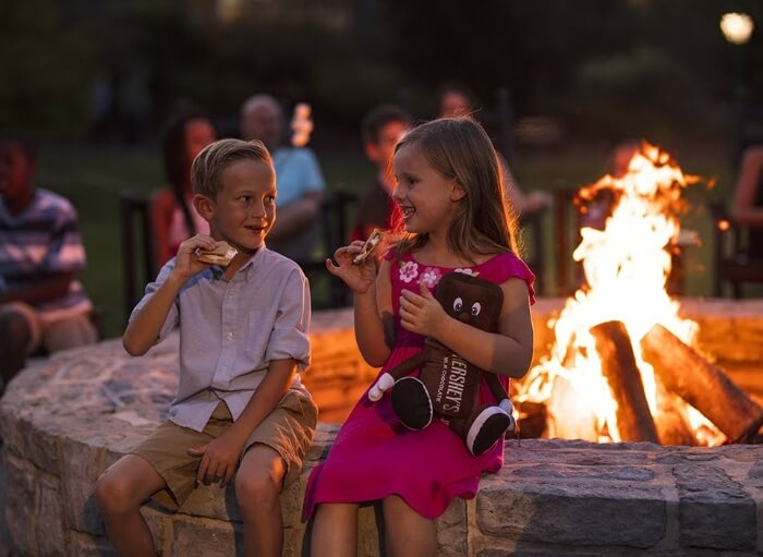 Kids eating smores by a fire