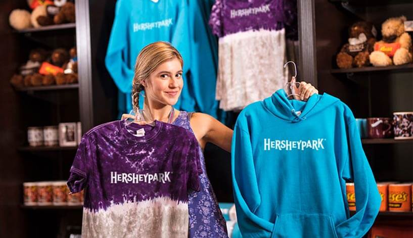 girl in a Hersheypark retail shop showing two versions of available Hershey's Kisses shirts