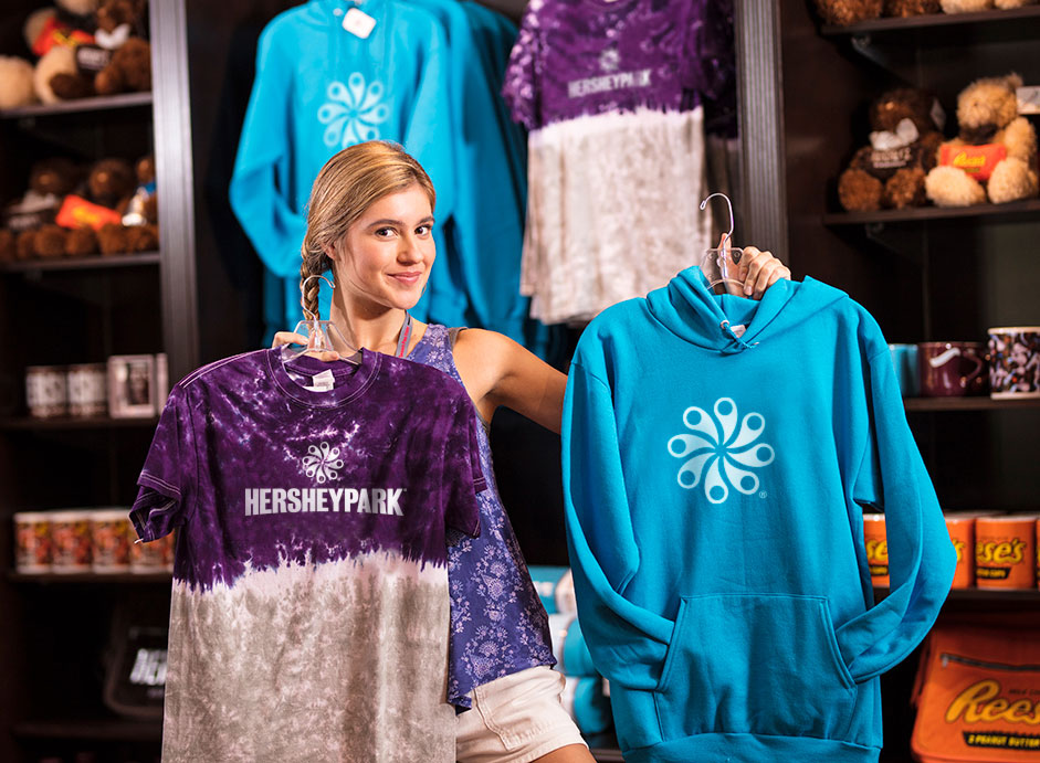 girl in retail store holding up Hersheypark shirts